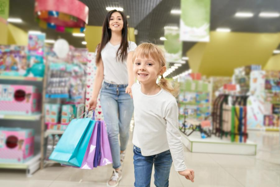girl-keeping-hand-mom-running-forward-toy-store